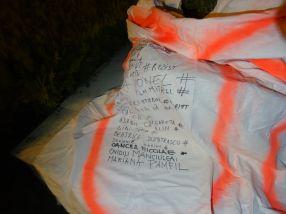 Oamenii îsi scriu numele pe cearsaful care va pleca la expozitia de la Cluj